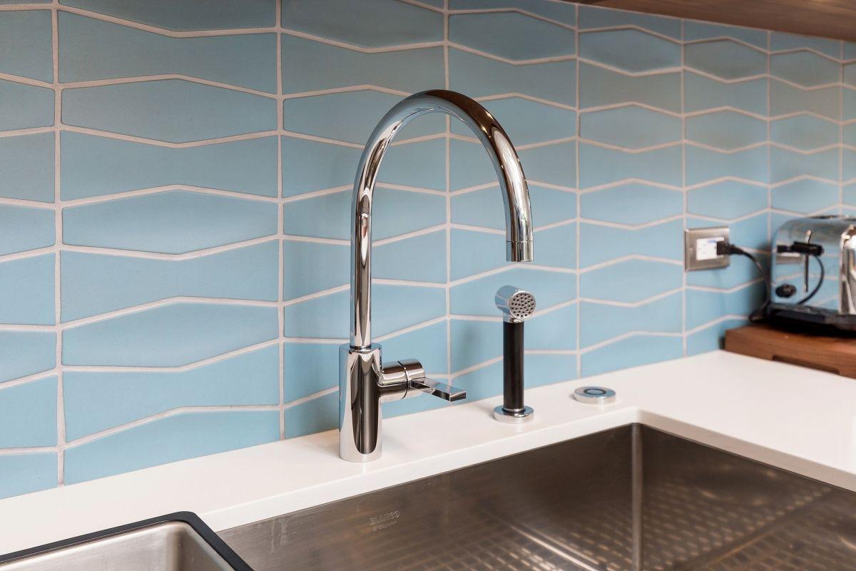 Kitchen Faucet Detail Against Blue Backsplash