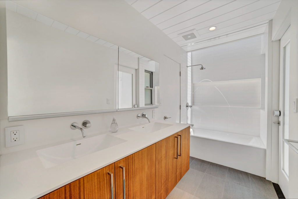 The long view of this restful bath space remodeled by Keycon with modern amenities and natural finishes