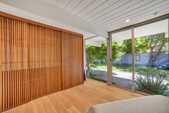 The restful sleep space in this Keycon-remodeled San Mateo Eichler has secret storage behind sliding panels